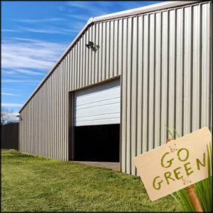 """Photo of a large prefab steel building with a sign saying, """"Go Green!"""""""