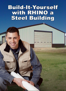 a smiling man holding building plans crouches before his finished RHINO steel building