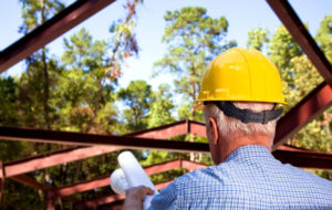 Photo of a man in a hard hat supervising the placement of a steel building rafter.