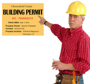 Builder in yellow hard hat points to a metal building permit.