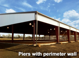 Photo of a riding arena with a pier and perimeter wall foundation.
