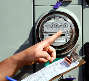 Photo of a hand pointing to a utility meter.