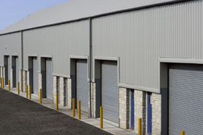 Photo of a gray metallic warehouse with stone trim.