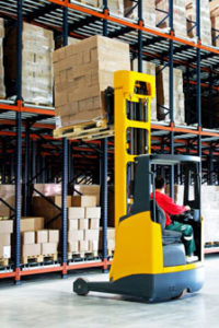 Photo of a warehouse worker using a forklift.