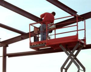 Man on a scissor lift assembling a RHINO steel building.