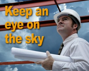 Man in hard hat carrying building plans keeps an eye on the sky to avoid dangerous lightning on a construction site