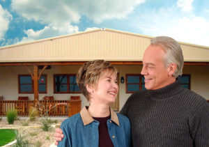 Photo of smiling senior couple before a RHINO steel-framed home.
