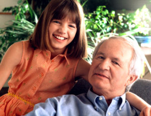Photo of a smiling granddaughter with her arm around her grandfather's neck.