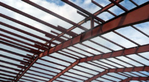 Photo of blue sky seen through steel rafters of a RHINO building under construction.