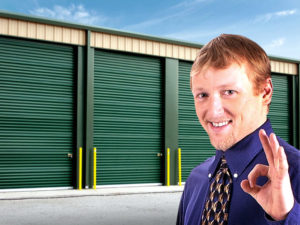 Happy business owner stands before steel building units at his self-storage facility.