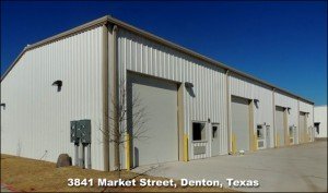 Attractive white industrial steel building with snappy tan trim and four bays