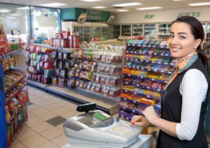 Smiling clerk awaits her next customer in a metal building convenience store.