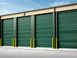 Photo of a tan self storage building with deep green roll-up doors.