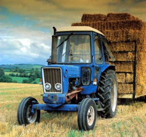 Photo of a blue tractor pulling a trailer of hay bales from the field.