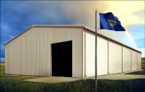 Large beige and tan-trimmed metal building under rainbow with Nebraska flag flying