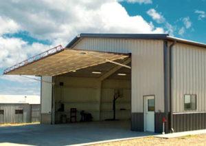 Photo of a RHINO steel hangar with a hydraulic hangar door.