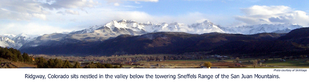 Glorious scenic view of Ridgway, Colorado nestles in a mountain valley beside towering snow-covered peaks