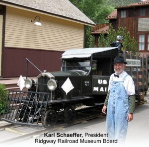 Karl Schaeffer stand by vintage railroad mail car at the Ridgway Railroad Museum in Colorado