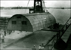Historical photograph of early Quonset hut being carried by a crane
