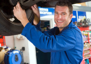Smiling mechanic mounting a tire.