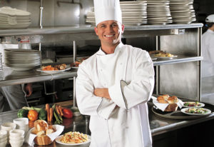 Photo of smiling chef in busy restaurant kitchen.