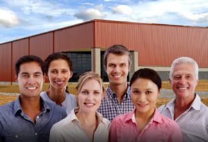 Happy workers stand before a prefabricated steel building.