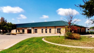 Photo of a brick commercial building with a green hip roof, built with a RHINO pre-engineered metal building.