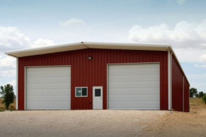 Photo of a red metal barn with white trim and two large overhead doors.