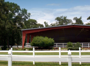 Photo of a large steel covered riding arena.