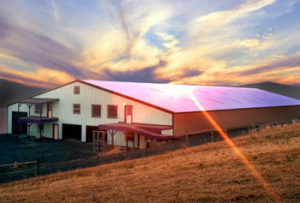 Photo of a large metal barn reflecting the sun's rays.