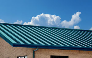 Photo of a bricked metal building with a blue-green metal roof panels.
