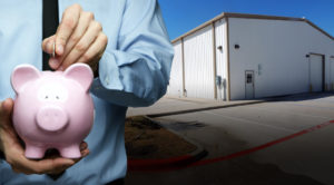 Photo of a man putting money in a piggy bank as he stands before his new metal building.