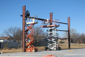 photo showing erectors using scissor lifts to assemble a steel building kit.