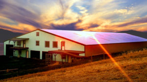 The sun sets over a huge rural metal building in Texas.