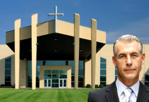 Pastor stands before beautiful metal church building.