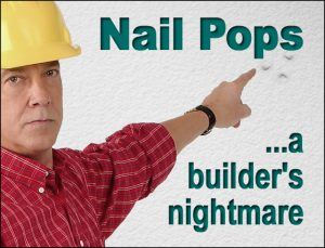 builder in bright yellow hard hat points to disfiguring  dry wall nail pops on wood-framed wall