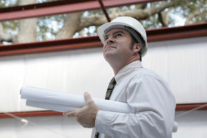 Photo of a builder overseeing the erection of his prefab steel building.