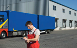 Photo of a warehouse worker and truck before a two-story metal building warehouse.