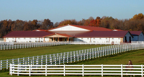 Photo of a gorgeous RHINO horse stables with a red metal roof.