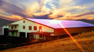Photo of a huge RHINO steel barn at sunset.