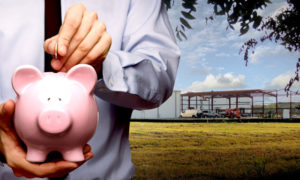 Photo of a man putting money in a piggy bank as he stands before his metal building under construction.