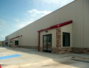 Photo of a tan RHINO commercial building with rock trim.