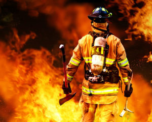 Firefighter holding tools faces an immense fire