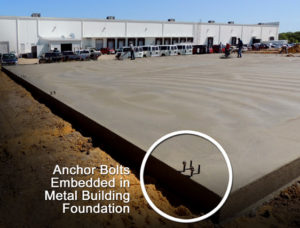 Photo shows a curing metal building foundation with anchor bolts embedded in the concrete.