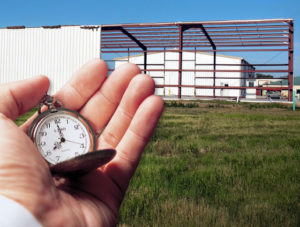 Steel building under construction with hand holding stopwatch in foreground.