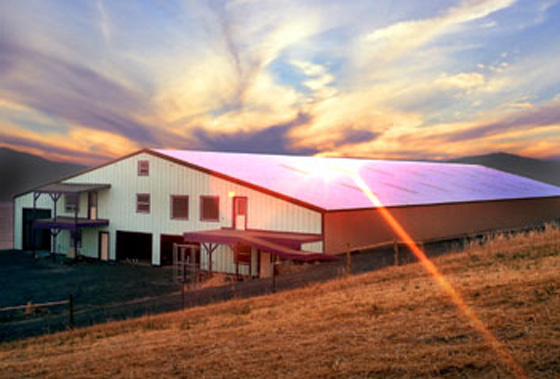 Photo of a large steel riding arena at sunset.