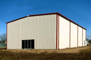 Photo of a tan RHINO steel building with rust-colored trim and gutters.