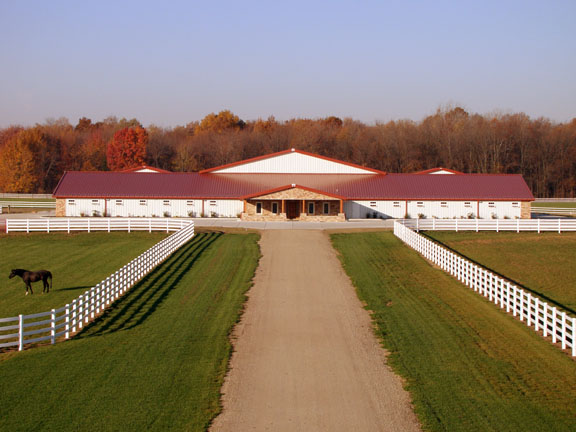 Photo of magnificent metal building horse stables and indoor riding arena.