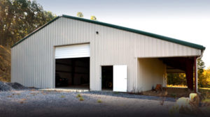 White steel barn with dark green trim and a shade shelter on the side.