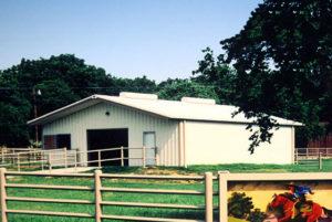 Photo of a RHINO metal barn with a rail fence around it.